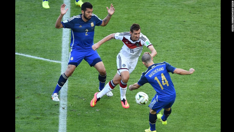 Klose, center, looks to split Garay, left, and Javier Mascherano.