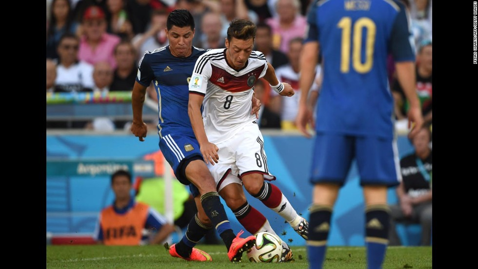German midfielder Mesut Ozil, center, tries to dribble past Argentine midfielder Enzo Perez in the first half.