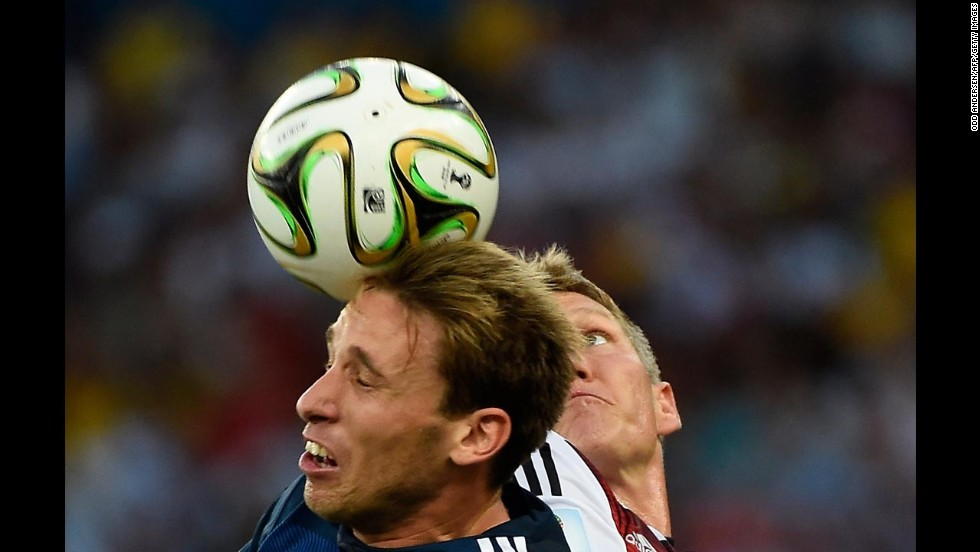 Biglia, left, and Schweinsteiger head the ball.