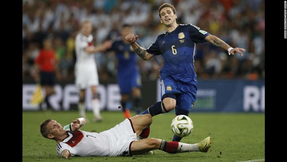 Schweinsteiger slides to tackle Argentina's Lucas Biglia.