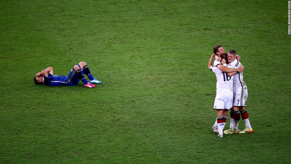 Argentina's Sergio Aguero lies on the ground as German players celebrate their victory.