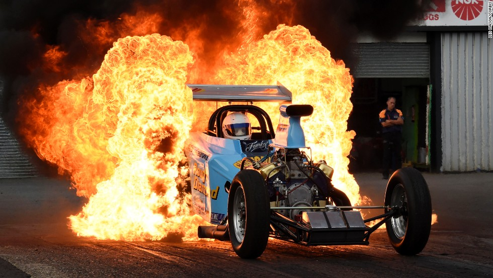 Flames are seen behind Bob Hawkins' car during a drag racing meet Saturday, July 12, at the Santa Pod Raceway in Podington, England. It is common to see fire under drag racing vehicles as their engines are pushed to the limit.