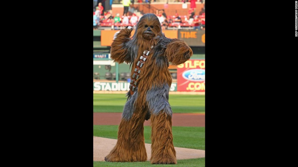 "A person dressed as ""Star Wars"" character Chewbacca throws out the first pitch prior to a Major League Baseball game in St. Louis on Wednesday, July 9. It was ""Star Wars Night"" at Busch Stadium."