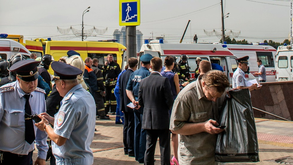 Police officers and rescuers crowd near an entrance to the Park Pobedy metro station.