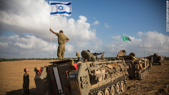 An Israeli soldier stands on top of an armored personnel carrier near the Israeli-Gaza border on July 15, 2014 near Sderot, Israel.