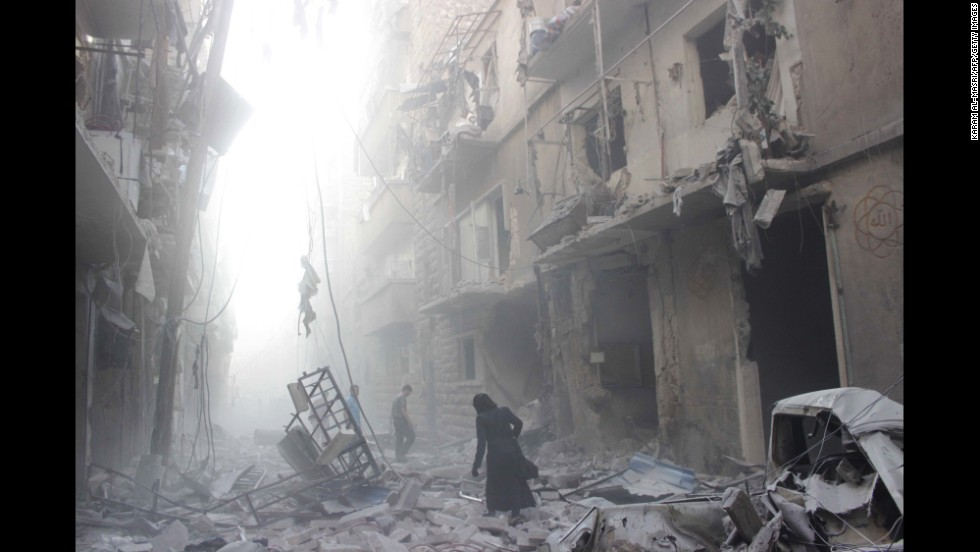 A woman walks amid debris after an airstrike by government forces July 15 in Aleppo.
