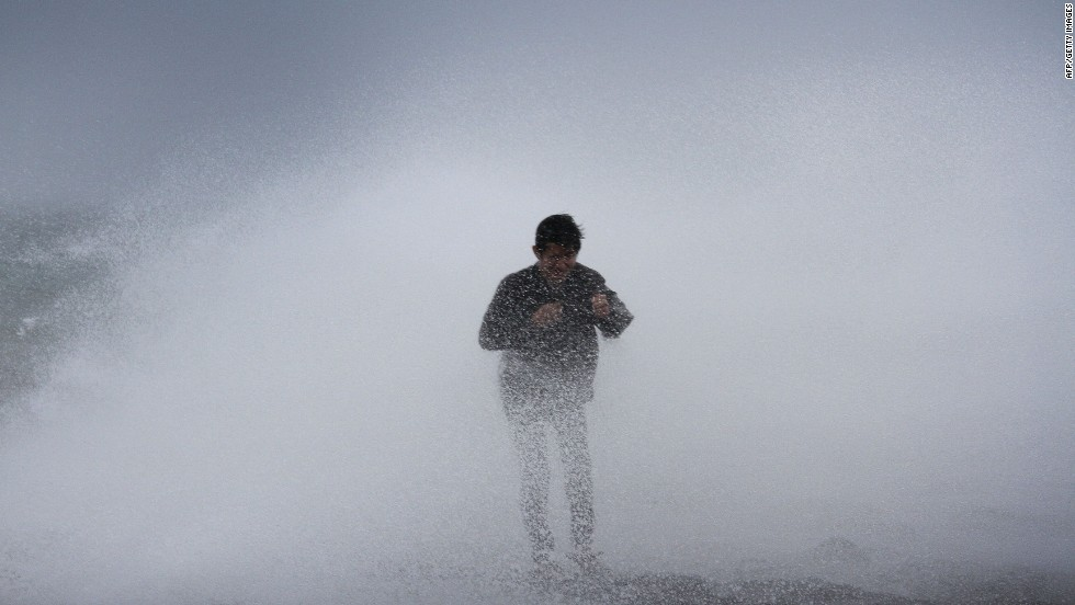 A resident stands near waves in Legazpi City, southeast of Manila, on July 15. Rammasun is expected to stay at category 3 strength until its final landfall near the China-Vietnam border.