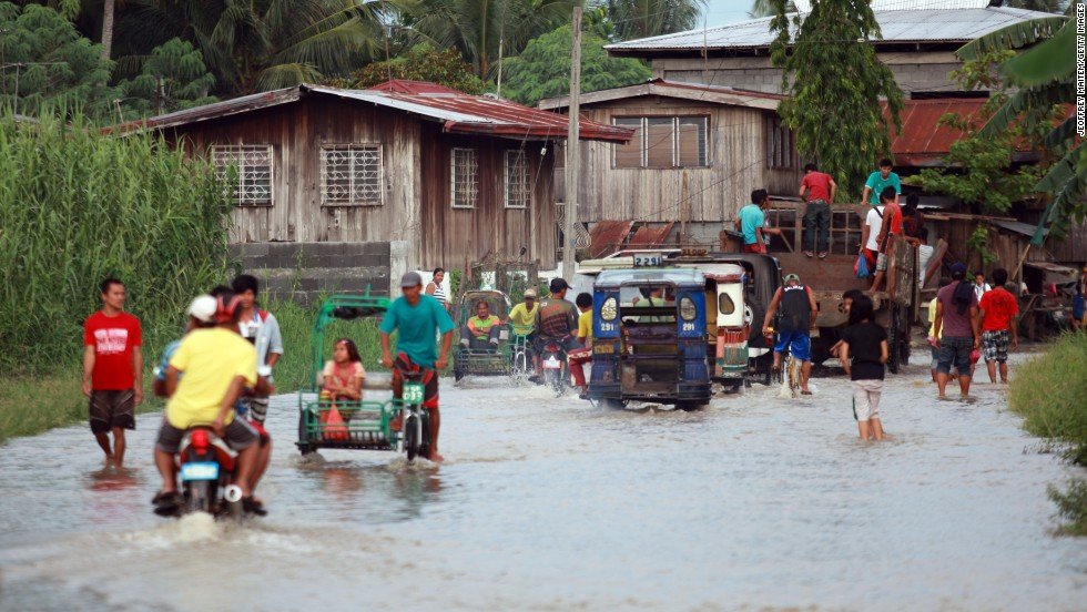Residents cross a flooded road on July 15 in Sultan Kudarat, Mindanao, Philippines. Mudslides and flooding are feared across the country.