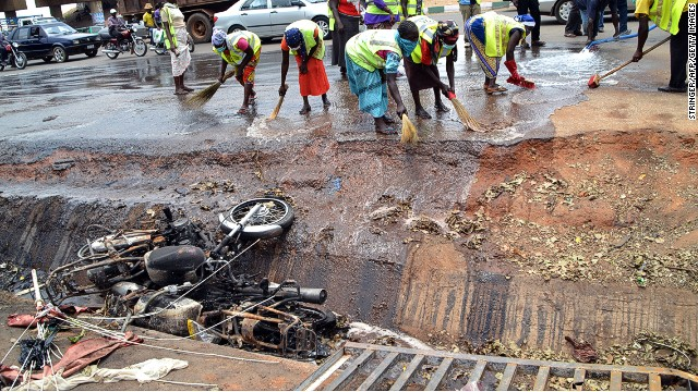 Nigerian workers clean the site of a bomb blast in Abuja on April 15, 2014.