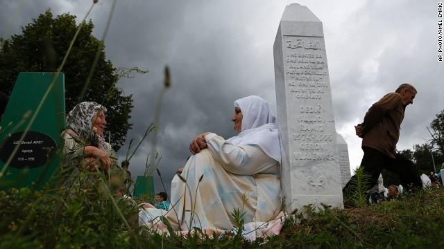 Bosnian Muslim women rest near a gravestone during a funeral in Srebrenica, Bosnia on Friday July 11, 2014. T