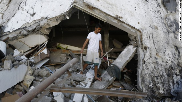 A Palestinian youth inspects a house after it was destroyed by an Israeli air strike early on July 16, 2014, in Gaza City.