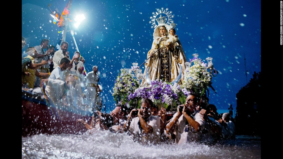 Carriers of the Great God Power brotherhood unload a Virgen del Carmen statue at the Puerto de la Cruz dock on the Canary island of Tenerife, Spain, on Tuesday, July 15. The procession with the statue of the patron saint of fisherman has taken place since 1921.