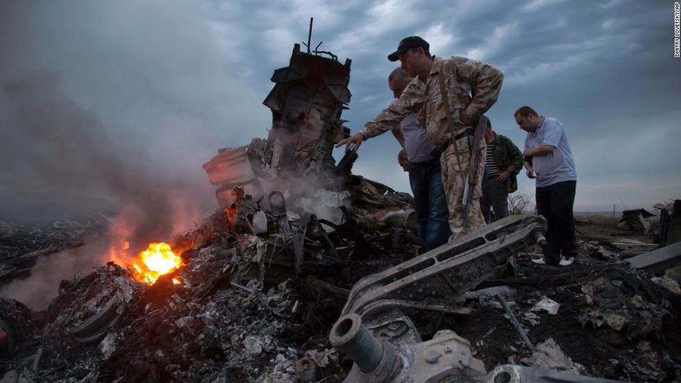 People inspect the crash site on Thursday, July 17, 2014.
