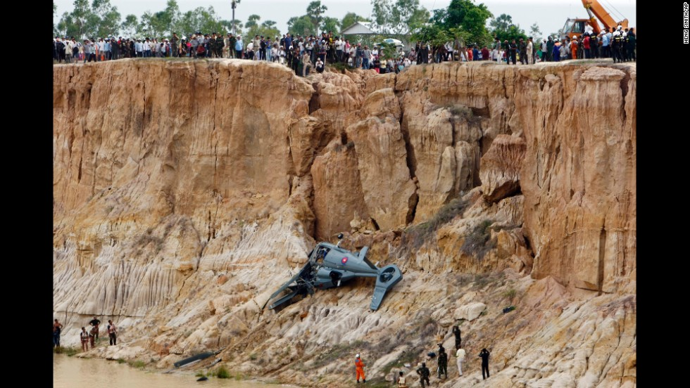 Soldiers use a crane to retrieve parts of a military helicopter from a pond after it crashed on the outskirts of Phnom Penh, Cambodia, on Monday, July 14. Four people were killed in the crash and a fifth person was seriously injured, according to media reports.