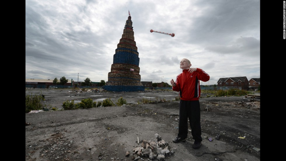 Curtis Walker throws a baton beside a Loyalist pyre before a bonfire in Belfast, Northern Ireland, on Friday, July 11. The 200-foot bonfire will mark the start of the 12th of July Orange parade, celebrating the protestant King William of Orange's victory over the Catholic English King James II at the Battle of the Boyne in 1690.