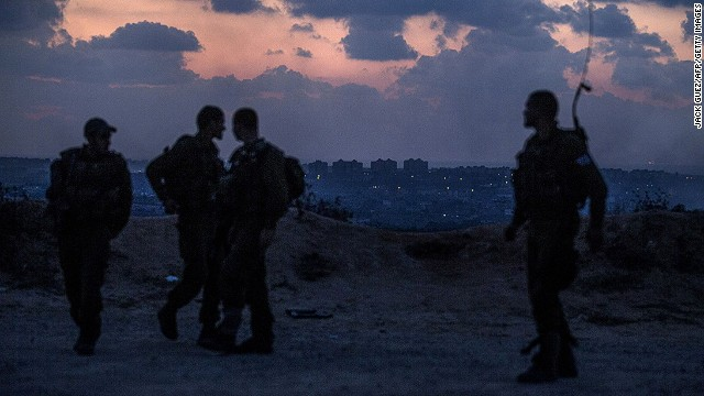 Israeli soldiers stand near the southern Israeli border with the Gaza Strip (background) on July 17, 2014.