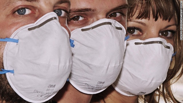 People wearing a medical face mask pose on July 30, 2009 in Lille, northern France. While the World Health Organisation (WHO) has stopped collating figures on infected numbers, European Union Health Commissioner Androulla Vassiliou predicted on July 18, 2009 that 60 million people across the 27-nation bloc would need priority vaccination