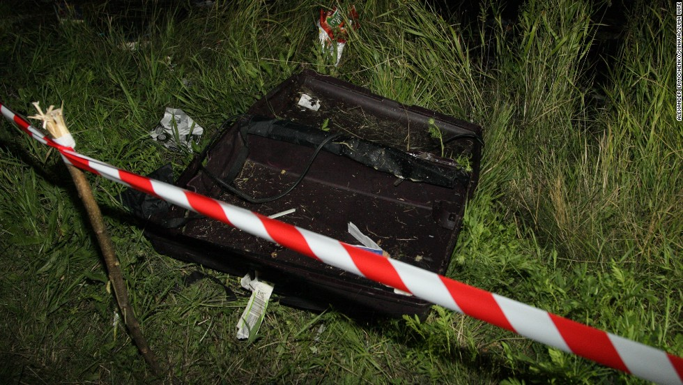 An empty suitcase is cordoned off near the plane's impact site on Thursday, July 17.