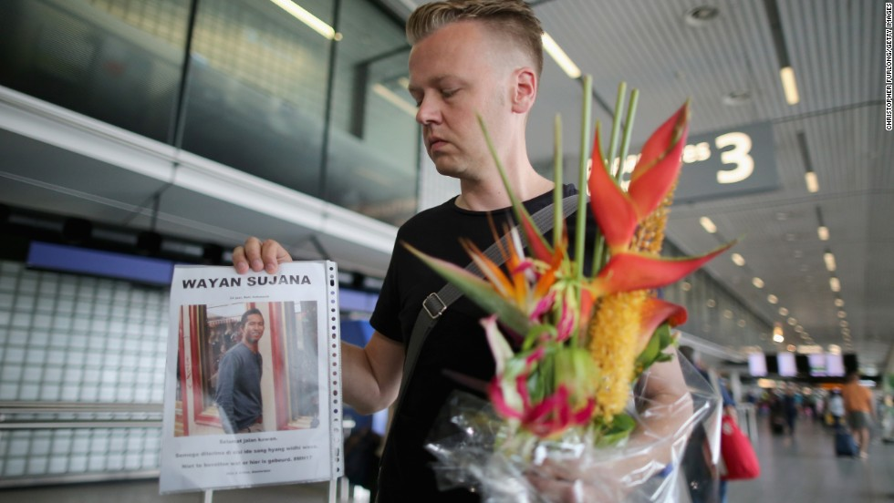 Arthur Laumann holds a floral tribute and photograph of family friend Wayan Sujana, believed to be missing on the flight, at Schiphol Airport on July 18 in Amsterdam.