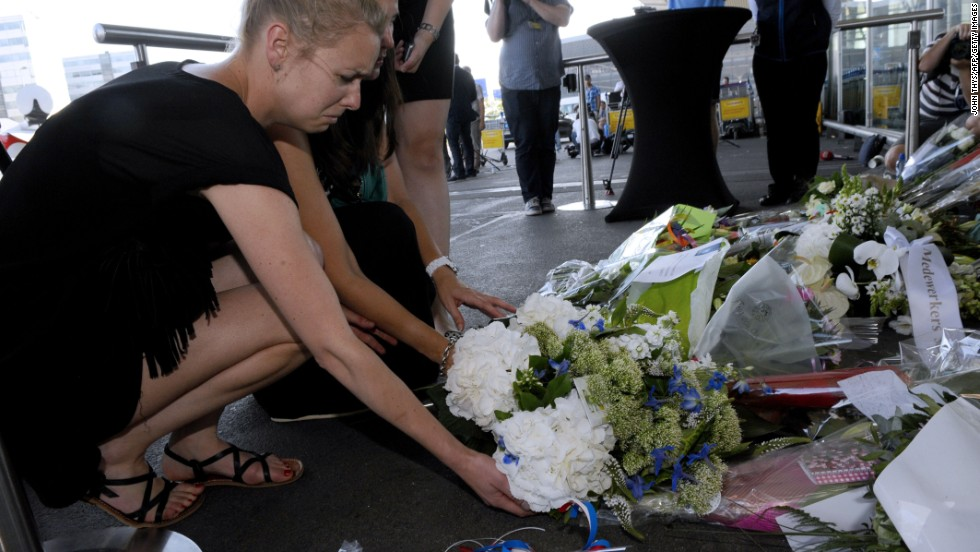 People lay flowers and light candles in front of the Schiphol airport on July 18.