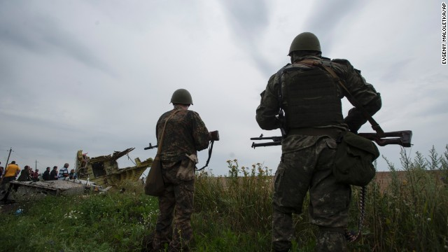 Pro-Russia fighters stand on guard as the OSCE (Organization for Security and Co-operation in Europe) delegation arrives at the crash site of a Malaysia Airlines jet near the village of Hrabove, eastern Ukraine, Friday, July 18, 2014.  Representatives from OSCE and four Ukrainian experts have traveled into rebel-controlled areas to begin an investigation into the downing of the Malaysia Airlines plane on Wednesday and the deaths of all its passengers and crew.  (AP Photo/Evgeniy Maloletka)
