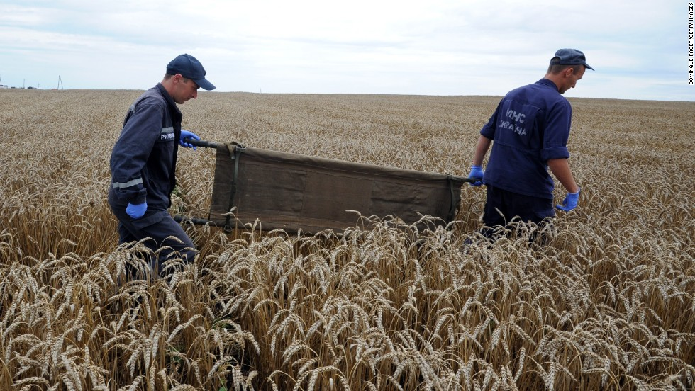 Ukrainian rescue workers walk through a wheat field with a stretcher as they collect the bodies of victims on July 19, 2014.