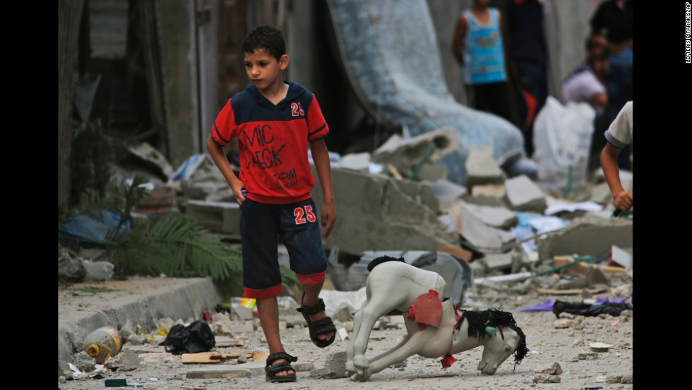 A Palestinian child walks on debris from a destroyed house following an overnight Israeli strike in Beit Lahiya on Saturday, July 19.