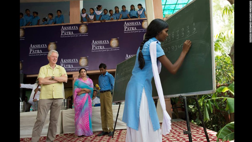 At Jaipur's Government Secondary Sanskrit School, Clinton watches as students solve math problems at the blackboard.
