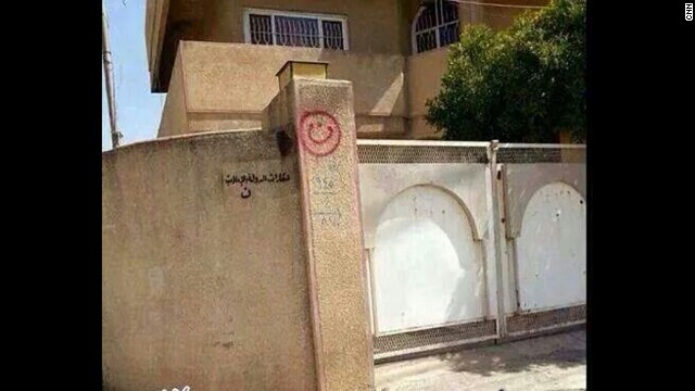 "A house in Mosul, Iraq, with ""property of ISIS"" painted on a wall."