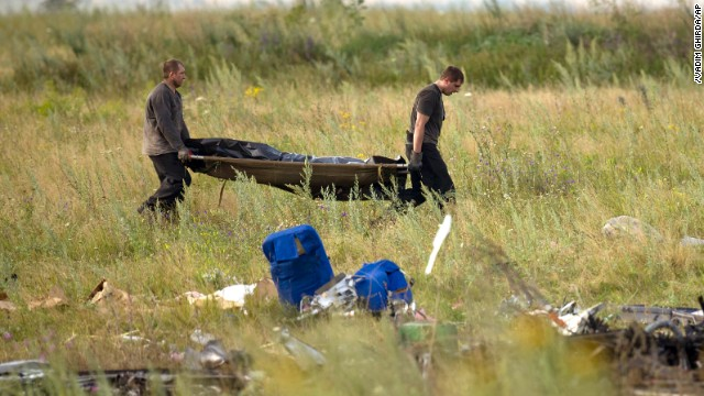 Emergency workers carry the body of a victim at the crash site of Malaysia Airlines Flight 17 in eastern Ukraine on Saturday, 19.