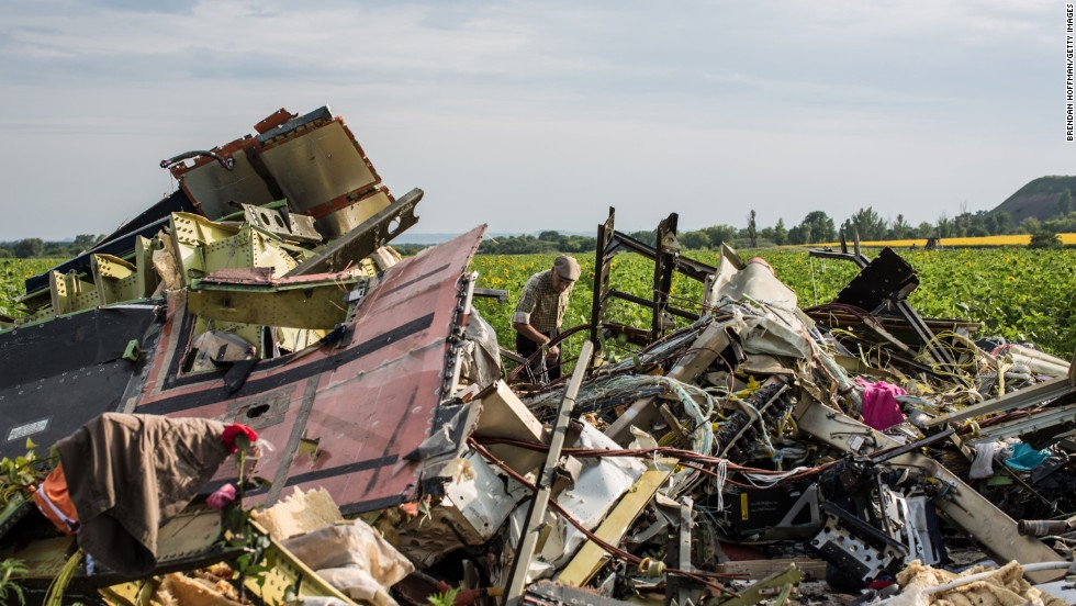 A man looks through the debris at the crash site on July 19, 2014.