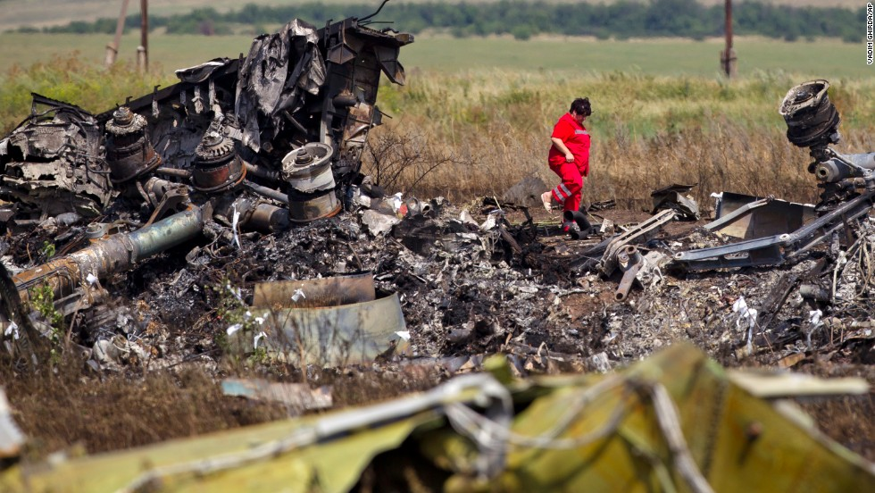 A woman walks among charred debris at the crash site on July 20, 2014.