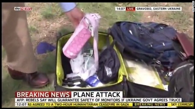 A reporter picks up the belongings of MH17 victims during a live Sky News broadcast at the crash site in eastern Ukraine.