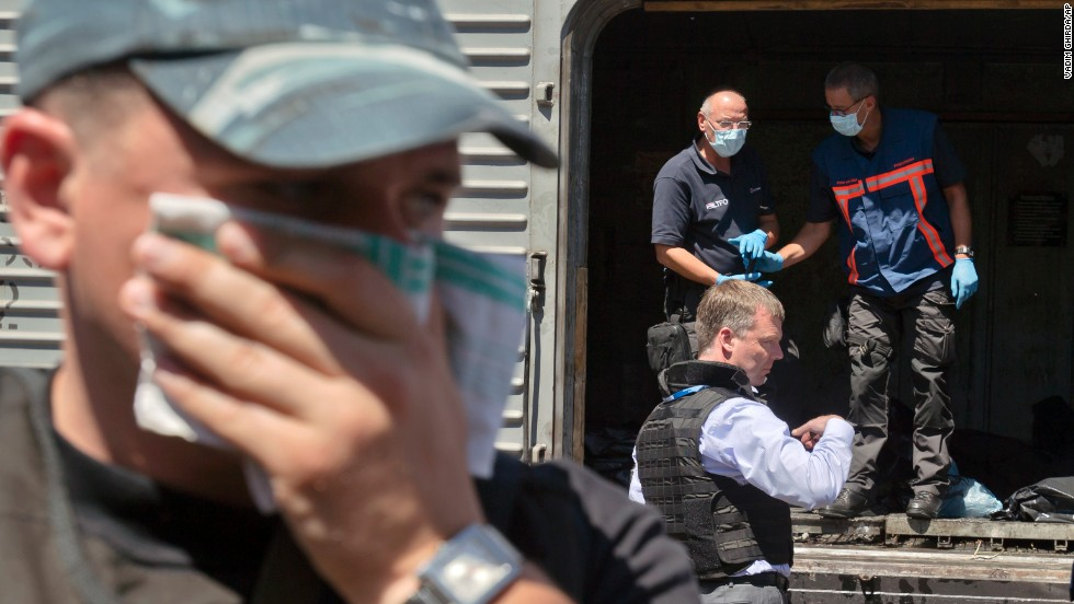 A man covers his face with a rag as authorities inspect bodies in a refrigerated train Monday, July 21.