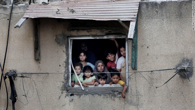 A Palestinian family watch rescuers searching for bodies and survivors under the rubble of a homes which were destroyed by an Israeli missile strike, in Gaza City, Monday, July 21, 2014.