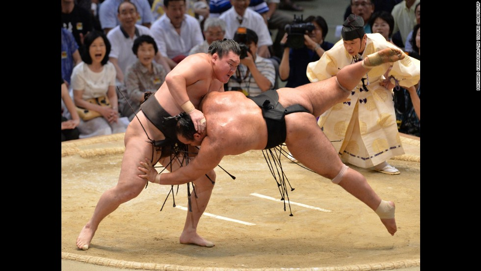 Mongolian sumo champion Hakuho, left, throws Osunaarashi at the Grand Sumo Tournament in Nagoya, Japan, on Sunday, July 20. Hakuho was seeking the 30th tournament victory of his career.