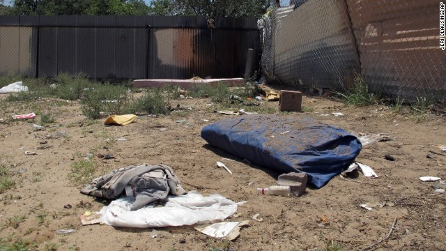 Bedding, clothing and broken glass litter a homeless encampment in Albuquerque where three teenagers are accused of fatally beating two homeless men.