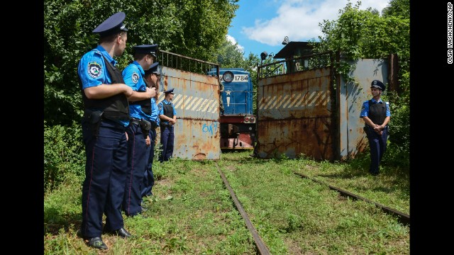 Police officers secure a refrigerated train loaded with the bodies of passengers from Malaysia Airlines Flight 17 as it arrives in a Kharkiv, Ukraine, factory on Tuesday, July 22.