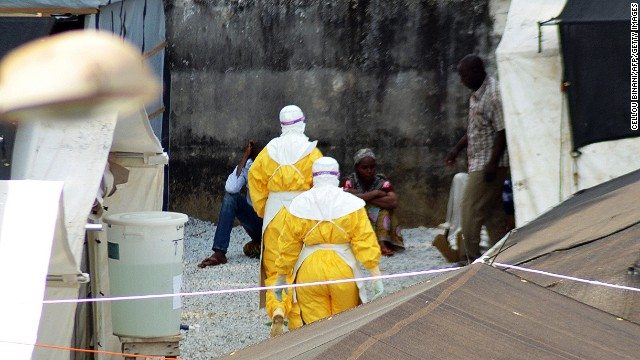 Health workers wearing protective suits walk in an isolation center for people infected with Ebola at Donka Hospital in Conakry