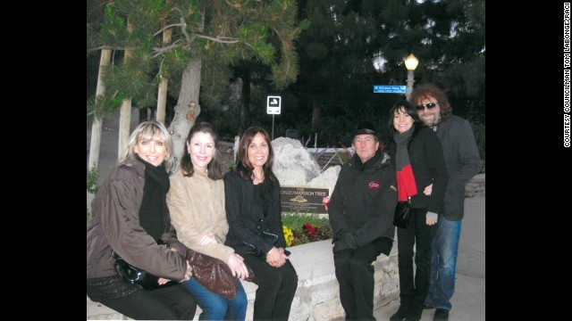 The George Harrison tree in LA's Griffith Park is behind family and friends including Harrison's widow, Olivia (center, in black), Eric Idle of Monty Python fame near her, and Jeff Lynne (far right) of ELO and Harrison's band The Travelling Wilburys. The tree was killed by an infestation of beetles.