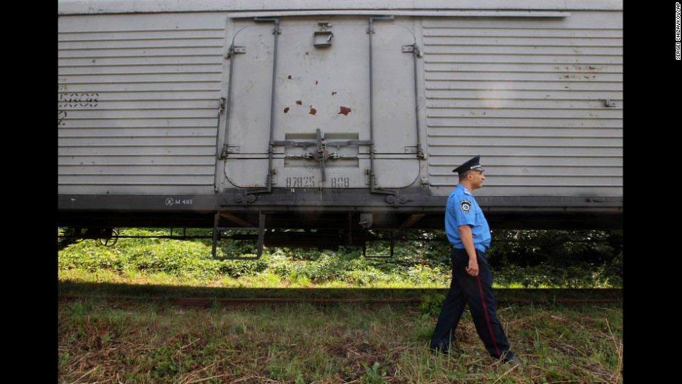 A police officer in Kharkiv walks past a refrigerated container car loaded with bodies on July 22.