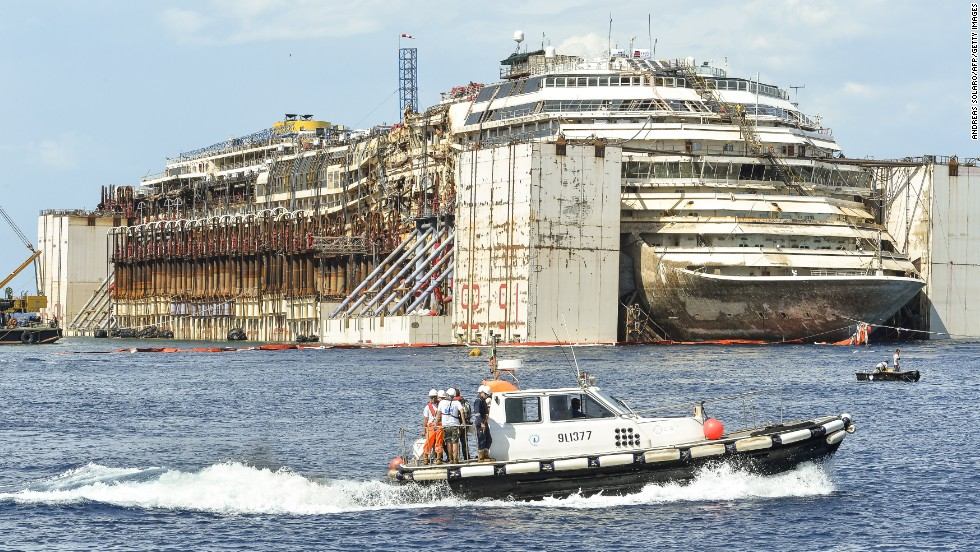 The Costa Concordia cruise ship sits in front of the harbor of Giglio Island after it was refloated using air tanks attached to its sides on Tuesday, July 22.  Environmental concerns prompted the decision to undertake the expensive and difficult process of refloating the ship rather than taking it apart on site.