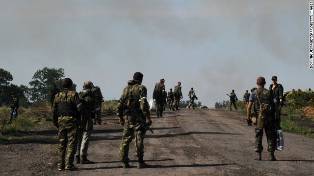 Pro-Russia militants march on a road after exchanging fire with the Ukranian army near the town of Marynivka, 100 km east of Donetsk, on July 16, 2014. EU leaders met on July 16 to decide on new sanctions against Russia and pro-Moscow separatists in east Ukraine as Kiev raises fears of an imminent invasion by thousands of Russian troops.