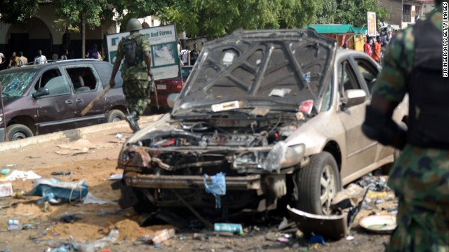 Military officers walk past a scene where a bomb exploded in Kaduna.