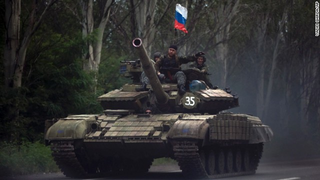 Pro-Russian rebels ride on a tank flying Russia's flag, on a road east of Donetsk, Monday, July 21, 2014. Another 21 bodies have been found in the sprawling fields of east Ukraine where Malaysia Airlines Flight 17 was downed last week, killing all 298 people aboard. International indignation over the incident has grown as investigators still only have limited access to the crash site and it remains unclear when and where the victims' bodies will be transported. (AP Photo/Vadim Ghirda)