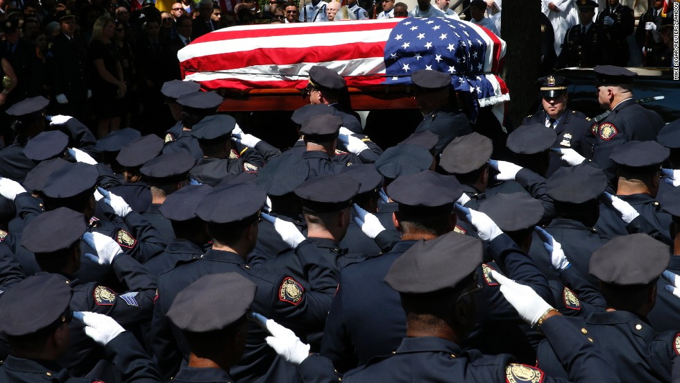 Police officers salute as the casket carrying slain police officer Melvin Santiago is carried into a church for his funeral service in Jersey City, New Jersey, on Friday, July 18. Santiago was shot and killed in his car after responding to an armed robbery call, officials said.