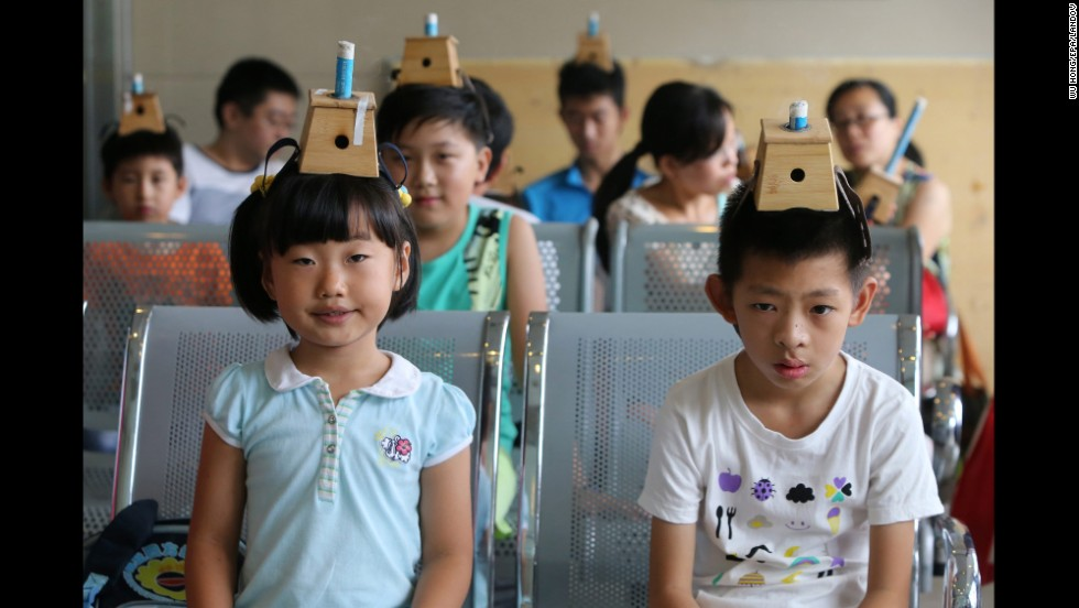 "Children wear moxibustion boxes on their heads Friday, July 18, at a hospital in Qingdao, China. Moxibustion is a traditional Chinese medical treatment that involves the burning of moxa, or mugwort. According to the <a href=""http://www.cancer.org/treatment/treatmentsandsideeffects/complementaryandalternativemedicine/manualhealingandphysicaltouch/moxibustion"" target=""_blank"">American Cancer Society</a>, practitioners believe the burning of the herbs can restore the balance and flow of vital energy, or chi. The children's treatment pictured here is part of an annual summer tradition to fend off winter diseases."