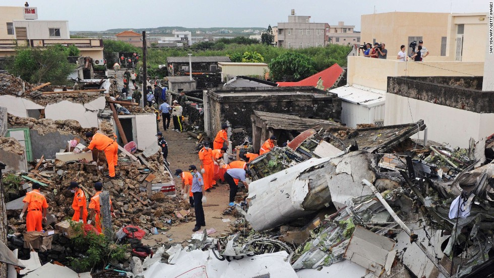 "Rescue workers survey the wreckage of TransAsia Airways Flight GE222 on the Taiwanese island of Penghu on Thursday, July 24. The plane was attempting to land in stormy weather but <a href=""http://www.cnn.com/2014/07/23/world/gallery/taiwan-plane-crash/index.html"">crashed on the island</a> late Wednesday, killing at least 48 people and wrecking houses and cars on the ground."
