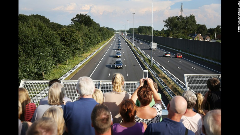 People watch from a bridge in Boxtel, Netherlands, as hearses carry victims to Hilversum, Netherlands, on Thursday, July 24.
