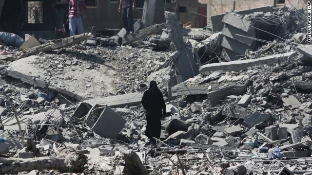 Palestinians through rubble on July 26 in Beit Hanoun.